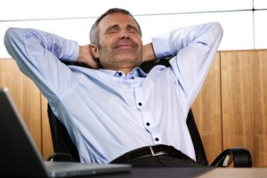 Happy senior businessman leaning back in his office chair.